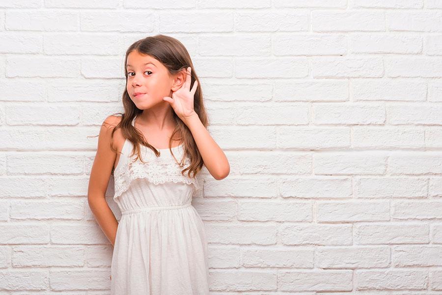 Niña con otitis serosa escuchando