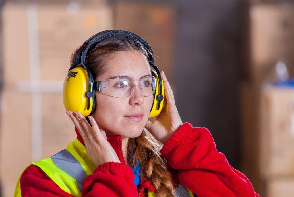 Trabajadora de la industria usando EPI auditiva