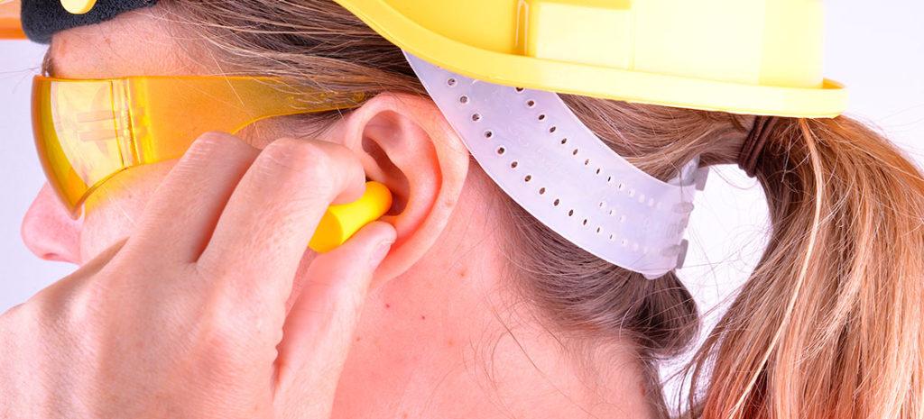 Operaria con tapones en los oídos para cancelar el ruido