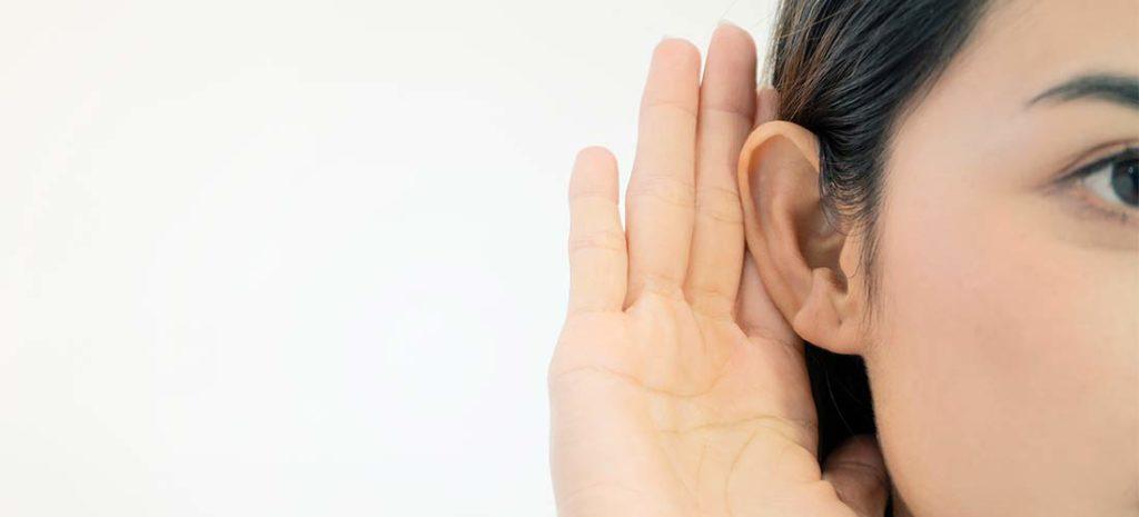Mujer oyendo con un audífono