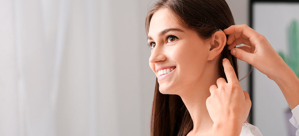 Mujer joven poniéndose un audífono en casa