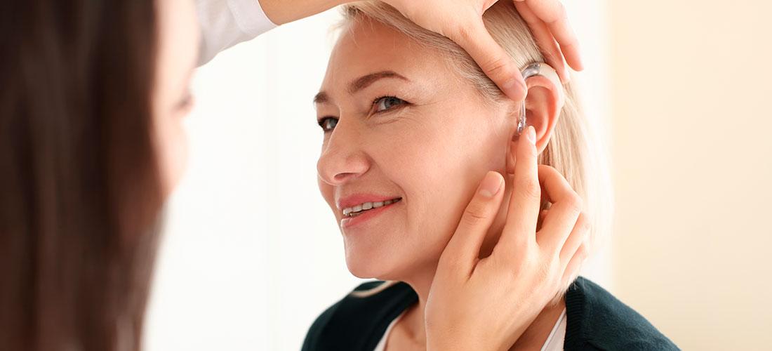 Mujer mayor con problemas de oído yendo al centro auditivo