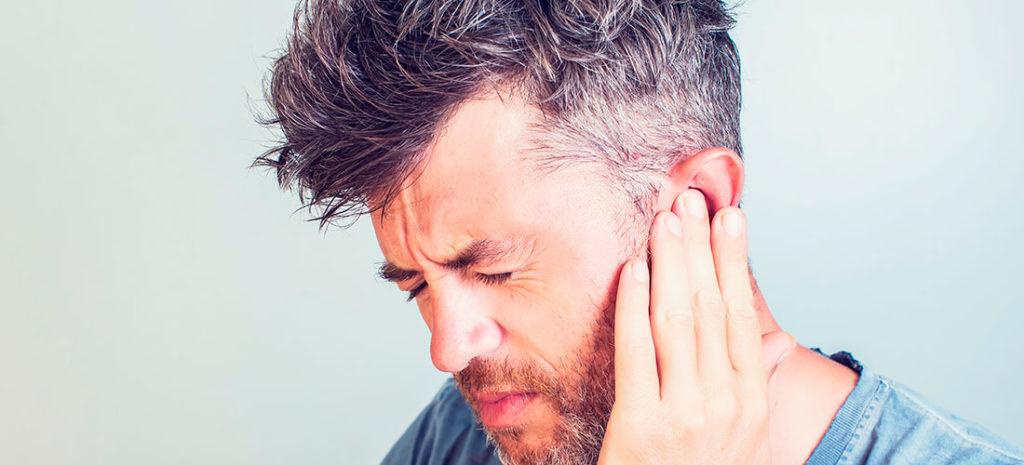 Hombre con dolor de oído o acúfenos